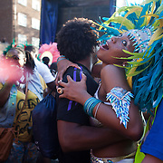 A female dancer shows her pleasure of being embrassed by a spectator. The Notting Hill Carnival has been running since 1966 and is every year attended by up to a million people. The carnival is a mix of amazing dance parades and street parties with a distinct Caribbean feel.