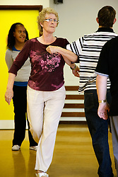 Woman Day Service Officer joining in line dancing with day service users with learning disabilities,