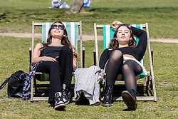 Licensed to London News Pictures. 19/04/2021. London, UK. Students, (left) Anais Laurent 19 and Lynn Allegre 18 soak up the sunshine in Hyde Park, London a week after the easing of Covid-19 restrictions as a mini heatwave hit the UK this week with temperatures reaching up to 18c in London and the South East. Photo credit: Alex Lentati/LNP