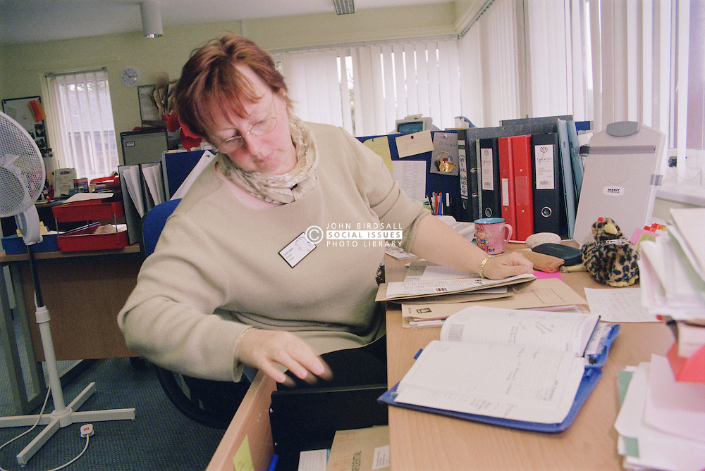 Woman working on Surviving Homelessness project looking in drawer of desk in office,