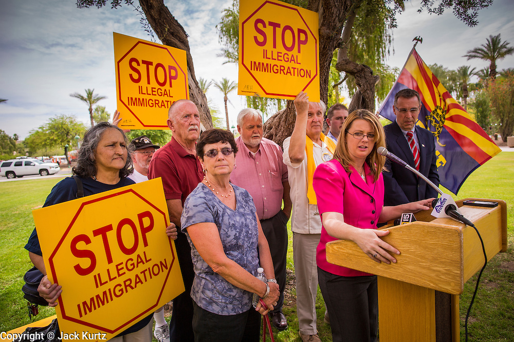 25 APRIL 2012 - PHOENIX, AZ:  KELLY TOWNSEND, (right, pink blouse) a member of the Tea Party, speaks at a press conference in support of SB1070 at the Arizona State Capitol Wednesday. Immigrants' rights groups opposed to SB1070 and Tea Party affiliated groups that support SB1070 gathered at the state capitol in Phoenix Wednesday to express their opposition and support of the bill. SB1070 was signed by Arizona Governor Jan Brewer in April 2010. At the time it was the toughest anti-illegal immigration bill in the country. Immigrants' rights groups sued Arizona and the federal courts stopped enforcement of the bill. The bill ended up in the US Supreme Court which heard arguments Wednesday. A ruling on the bill is expected in June.    PHOTO BY JACK KURTZ