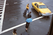 People and a yellow cab in the rain