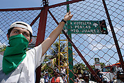 10 SEPTEMBER 2003 - CANCUN, QUINTANA ROO, MEXICO: An anti-globalization protestor opposed to the World Trade Organization and globalization hangs off of a fence separating the downtown area from the hotel zone in Cancun, Quintana Roo, Mexico during a protest against the WTO. Tens of thousands of people opposed to the WTO have come to this Mexican resort city to protest the 5th Ministerial meeting of the World Trade Organization. The WTO meetings are taking place in the hotel zone of Cancun, about 10 miles from the protestors.  PHOTO BY JACK KURTZ