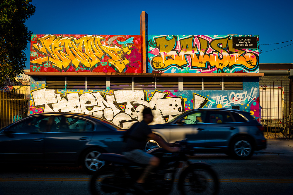 Traffic zips by a graffiti-covered, Art Deco building in Miami's Wynwood district
