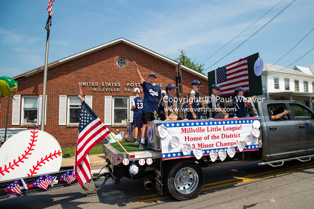 A Little League district champion baseball team rides on the back of truck in the Independence Day parade in Millville, Pennsylvania on July 5, 2021.