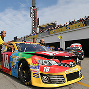 Crewmembers of NASCAR Sprint Cup driver Kyle Busch (18) are seen pushing his car to inspection during the practice session prior to the NASCAR Sprint Unlimited Race at Daytona International Speedway on Saturday, February 16, 2013 in Daytona Beach, Florida.  (AP Photo/Alex Menendez)