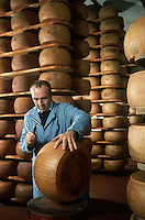 1989, Parma, Italy --- Inspector Tapping Wheel of Parmesan Cheese --- Image by © Owen Franken/CORBIS