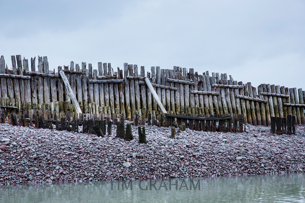 Timber groynes constructed to stop erosion ( groines ) of sand and pebbles at Porlock Weir in Somerset, United Kingdom