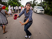 31 AUGUST 2014 - SARIKA, NAKHON NAYOK, THAILAND: A Thai woman dances in the street during a parade to honor Ganesh at Shri Utthayan Ganesha Temple in Sarika, Nakhon Nayok. Ganesh Chaturthi, also known as Vinayaka Chaturthi, is a Hindu festival dedicated to Lord Ganesh. It is a 10-day festival marking the birthday of Ganesh, who is widely worshiped for his auspicious beginnings. Ganesh is the patron of arts and sciences, the deity of intellect and wisdom -- identified by his elephant head. The holiday is celebrated for 10 days, in 2014, most Hindu temples will submerge their Ganesh shrines and deities on September 7. Wat Utthaya Ganesh in Nakhon Nayok province, is a Buddhist temple that venerates Ganesh, who is popular with Thai Buddhists. The temple draws both Buddhists and Hindus and celebrates the Ganesh holiday a week ahead of most other places.    PHOTO BY JACK KURTZ