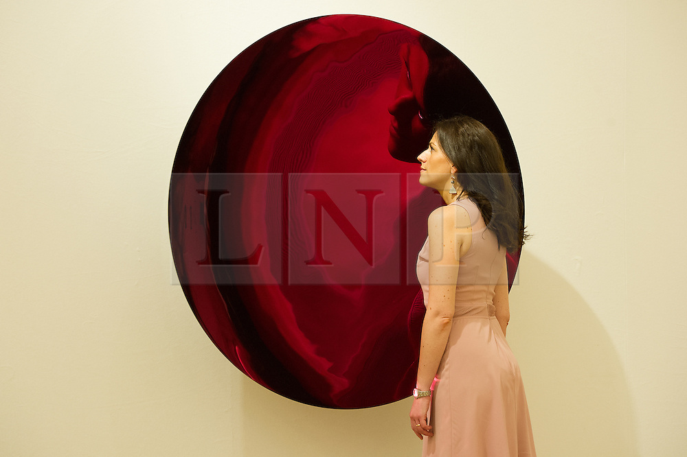 © London News Pictures. 26/06/15. London, UK. A Bonham's employee looks at Anish Kapoor's 2012 'Untitled', a monumental concave disc in stainless steel, coated in a magenta enamel, which is part of Bonhams Contemporary Art Sale, New Bond Street, Central London. Photo credit: Laura Lean/LNP