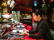 29 JANUARY 2016 - BANGKOK, THAILAND: Workers set up the counter before opening at L'atelier de Joel Robuchon, an exclusive French restaurant owned by French chef Joel Robuchon. The restaurant features counter style seating which looks into the kitchen so diners can watch the creative process involved in preparing their food.          PHOTO BY JACK KURTZ