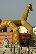 A Kuwaiti man in a traditional thaub walks toward a bouncy castle decorated with a giant giraffe along the Sharq promanade in Kuwait City.