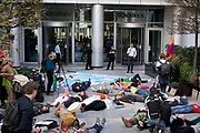 Black Rock employees watch the protest outside the offices of the company, during a 'die in.' Extinction Rebellion and APIB staged a protest on the global day to protect the Amazon, outside Black Rock investments in the City of London, Moorgate, London. Activists did performances and staged a 'die in' on the ground outside the company.