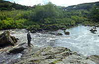 Fisherman, rock-strewn river, between villages of Carrick & Teelin, Co Donegal, Rep of Ireland, 199908096..<br />