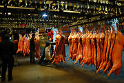 Workers examine and move pig carcasses at a meat wholesale and distribution center in Shanghai, China on 03 March, 2011.  Inflation, especially the persistent rise of food prices, has been a major conversation topic for China's masses and concern for its leaders as inflation often lead to political instability throughout China's history.