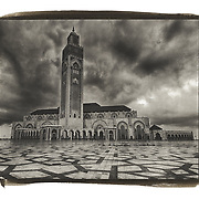 Viewed over a huge plaza made of granite stone on a dark and cloudy day, the Hassan II Mosque in Casablanca, Morocco is one of the largest mosques in the world.