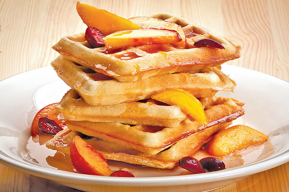 waffles stacked with fresh fruut topping on white plate on wooden table