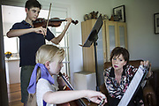 Mary Finsterer composer of concert and film music and recognized as one of Australia's most original orchestral composers at home in Bowral with children Wil Golja on violin and Eve Golja on Cello.