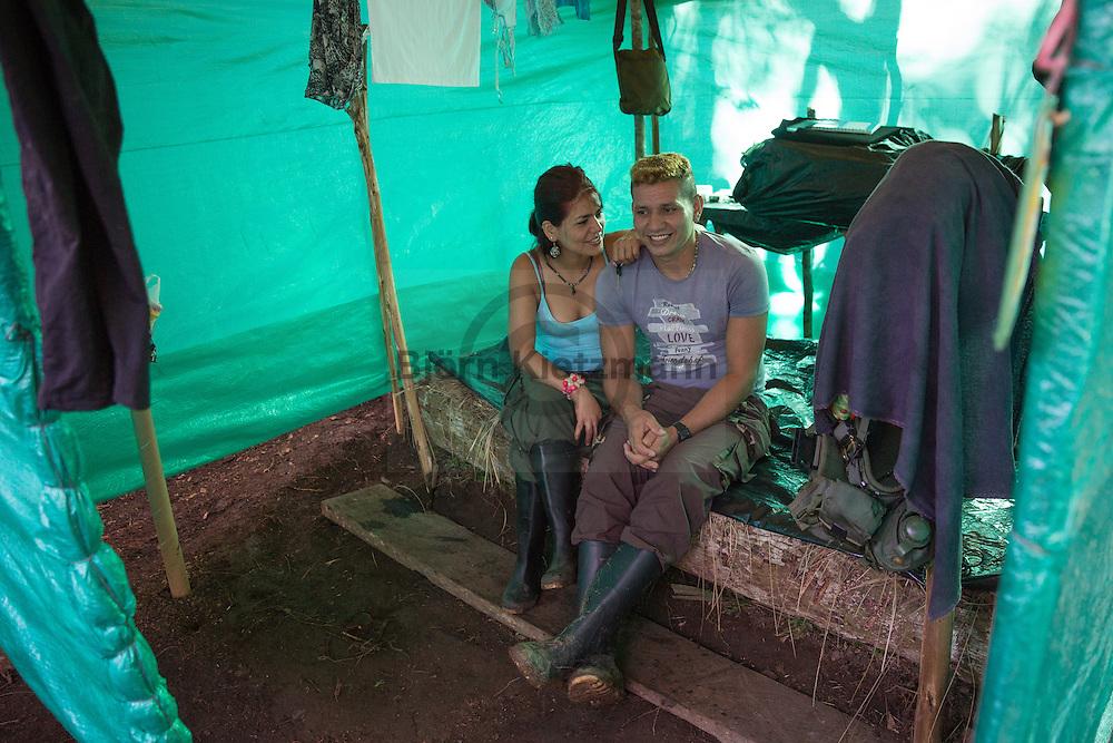 El Diamante, Meta, Colombia - 15.09.2016        <br /> <br /> A guerilla couple sitting on a bed inside their booth. Guerilla camp during the 10th conference of the marxist FARC-EP in El Diamante, a Guerilla controlled area in the Colombian district Meta. Few days ahead of the peace contract passing after 52 years of war with the Colombian Governement wants the FARC decide on the 7-days long conferce their transformation into a unarmed political organization. <br /> <br /> Ein Guerilla Paerchen sitz auf dem Bett in ihrem kleinen Unterschlupf. Guerilla-Camps zur zehnten Konferenz der marxistischen FARC-EP in El Diamante, einem von der Guerilla kontrollierten Gebiet im kolumbianischen Region Meta. Wenige Tage vor der geplanten Verabschiedung eines Friedensvertrags nach 52 Jahren Krieg mit der kolumbianischen Regierung will die FARC auf ihrer sieben taegigen Konferenz die Umwandlung in eine unbewaffneten politischen Organisation beschließen. <br />  <br /> Photo: Bjoern Kietzmann