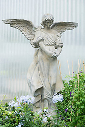 Angel statue with plants in garden centre, Augsburg, Bavaria, Germany
