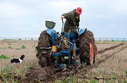 © Licensed to London News Pictures. <br /> 30/11/2014. <br /> <br /> Boulby, United Kingdom<br /> <br /> A competitor adjusts his plough as he takes part in a ploughing match that takes place each year on fields next to the picturesque Yorkshire coastline near Staithes. Farmers attend each year to demonstrate their ploughing skills and to help raise money for charity with proceeds from this year going to Charlie Brown Cancer Care in Newcastle.<br /> <br /> <br /> Photo credit : Ian Forsyth/LNP