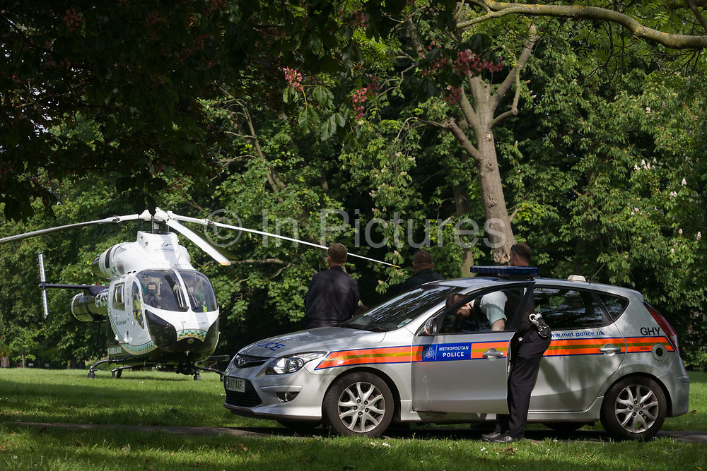 Met police and MD902 Explorer helicopter from the Kent, Surrey & Sussex Air Ambulance Trust on the ground in Ruskin Park after emergency flight to Kings College Hospital in south London. Standing by, a Met police officer looks for something inside his squad car before the crew return from accompanying the patient to A&E and the aircraft lifts off again for another emergency case. The Air Ambulance (KSSAAT) fly state of the art Helicopter Emergency Medical Service (HEMS) aircraft operating 365 days a year, out of their base at Marden in Kent and Redhill in Surrey. They're capable of delivering our crews anywhere in our region in under 20 minutes flying time, attending over 20,000 missions