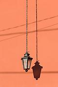 An electric lamp hangs on a chain against a salmon pink wall. Antigua Guatemala, Republic of Guatemala. 02Mar14