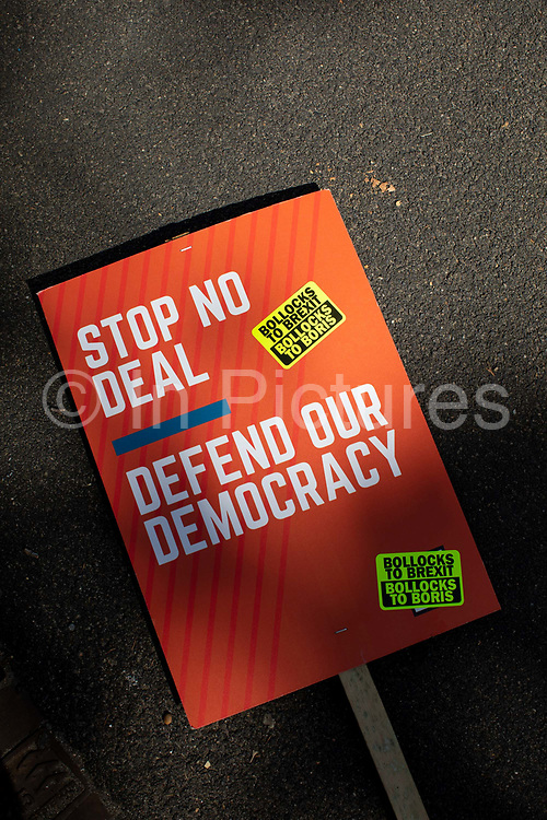 A Defend Our Democracy placard during the Stop The Coup protest against the proroguing of Parliament on 31st August 2019 in London in the United Kingdom. Left-wing group Momentum and the Peoples Assembly coordinated a series of Stop The Coup protests across the UK today, aimed at Boris Johnson and the UK government proroguing Parliament.