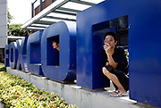 Employees at Hon Hai's Foxconn plant peek out from the back of a company sign in Shenzhen, China, on Wednesday, May 26, 2010. Hon Hai is the parts supplier for many hi-tech companies around the world including Apple Inc., Hewlett-Packard Co. and Dell Inc. There have been 12 suicides at the company's 300 thousand employee strong factory complex in Shenzhen so far this year. Foxconn has since moved some of its operations further inland to be closer to labor pool as well as cut costs.