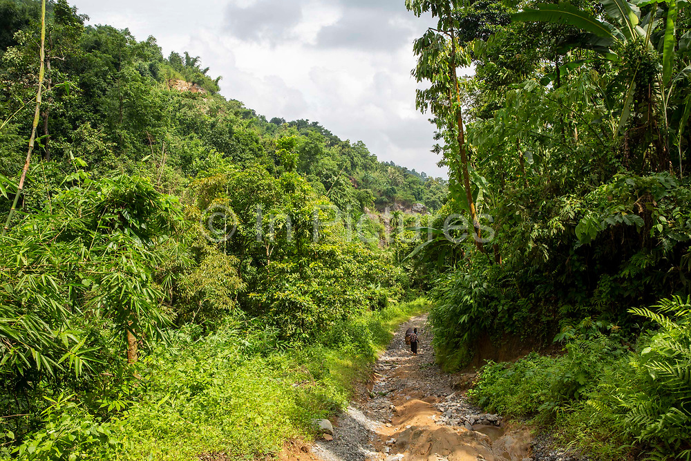 A woman walks down a steep rugged path towards a remote village on 21st September 2018 in Umling, Ri Bhoi, Meghalaya, India.