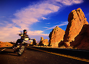 A motorcylist flys down a secluded desert road in Arizona