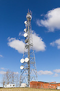 Urban provincial  cellular, microwave and telecom communications systems lattice tower under blue sky with cumulus cloud in Orange, New South Wales, Australia. <br />