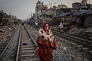A woman wearing a face mask to protect herself from air pollution walks along railway tracks in Dhaka, Bangladesh, April 29, 2019. The city has one of the worst quality of air on earth where dust, fumes and smoke can cause irreversible chronic respiratory diseases, lung cancer, heart complications or brain damage.