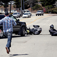 An off-duty Capitola, California police officer runs to assist one of his department's motorcycle officers as that officer hits the ground when his bike is hit by the truck at left as he responds to a pedestrian being hit in a Bay Avenue crosswalk in Capitola on Tuesday June 3, 2014. The motorcycle officer was transported to Dominican Hospital and released later the day with minor injuries. The woman hit in the crosswalk sustained non-life threatening injuries.<br /> Photo by Shmuel Thaler <br /> shmuel_thaler@yahoo.com www.shmuelthaler.com