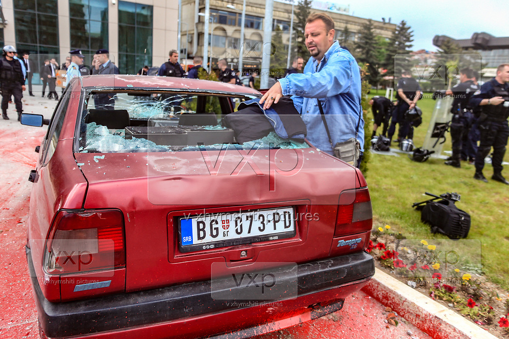 """Protestors threw bottles of red paint at the Government building and Borislav Stefanovic's vehicle chanting """"shame, shame"""" to express their opposition to the visit of the Head of Serbia's negotiating team in the Belgrade-Pristina dialogue Borislav Stefanovic, who arrived in Kosovo's capital Pristina in a first official visit since the 1999 Kosovo war on Thursday, May 12, 2011. Kosovan police in riot gear fired tear gas and used batons on Thursday to disperse a crowd of some one hundred ethnic Albanians that threw rocks and cans filled with red paint at police during the protest. (Photo/ Vudi Xhymshiti)"""