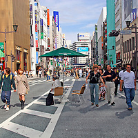 Asia, Japan, Tokyo. Shoppers stroll the Ginza district avenue of retail shops and department stores.