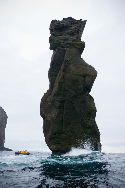 A zodiac boat passes Baily Head where a rock needle protrudes from the sea as surf crashes on the black sand beach nearby on Half Moon Island, home to over 3000 pairs of chinstrap penguins, many with chicks at this time of year, late in the Antarctic summer.