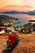 Older couple sitting on the top of Chora Mountain looking across the harbour of Ormos, Ios,  Cylades Islands, Greece .<br /> <br /> Visit our GREEK HISTORIC PLACES PHOTO COLLECTIONS for more photos to download or buy as wall art prints https://funkystock.photoshelter.com/gallery-collection/Pictures-Images-of-Greece-Photos-of-Greek-Historic-Landmark-Sites/C0000w6e8OkknEb8