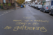 Road markings warn shoppers of wearing facial coverings and no close gatherings when the weekly street market on Northcross Road is open on Saturdays in East Dulwich, during the second wave of the Coronavirus pandemic, on 25th December 2020, in London, England.