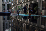 Financial services women walk through reflected light from a nearby skyscraper in the City of London, the capitals financial district aka the Square Mile, on 17th May 2018, in London, UK.