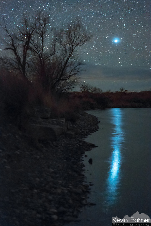 """At 2AM Sirius was casting a long, shimmering reflection on the Bighorn River just before it set. With a magnitude of -1.5, Sirius is the brightest star in the night sky. And at a distance of 8.6 light years away, it's the 8th closest to Earth. Under certain atmospheric conditions when it's low on the horizon this star is known to twinkle wildly and flash a wide range of colors. This happens more often than other astronomical objects because of it's brightness (planets do not twinkle). Sirius is found in the constellation of Canis Major and is also called the Dog Star. The ancient Greeks used to watch for the first appearance of Sirius in July, which marked the beginning of the """"dog days of summer,"""" the hottest part of the year."""