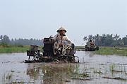 PEASANT FARMING, Malaysia. Peasant farmers working mechanical ploughs, in padi, Kedah State. World Bank funded  project. Poor farmers, peasants, planting, harvesting, cultivating rice padi.