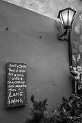 """Luino, Lombardia. ITALY.   """"Luino Old Town"""" <br /> <br /> """"Skip a Stone, Take a Hike, Sit a Spell, Just Breath, This is Lake Life"""". <br /> <br /> Chalk Board Quote hanging and lite by a lantern style light outside a Bar/Restaurant, situated in the steep hilly narrow streets,  on the side of Lake Maggiore, Province of Varese.. ITALY <br /> <br /> <br /> Monday  02/01/2017  <br /> <br /> © Peter SPURRIER,<br /> <br /> <br /> LEICA CAMERA AG LEICA Q (Typ 116). ISO 100  f1.7  28mm"""