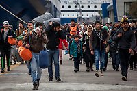 ATHENS, GREECE - FEBRUARY 04: Thousands of refugees walk on the Pireaus port after disembarking the ferry where they travelled from the Greek islands to Athens on February 04, 2016 in Athens, Greece. Thousands of refugees arrive every day at the Pireaus port from the Greek Islands where buses are waiting for those who paid for the trip in the FYROM border. Refugees without money are stranded at the port, where dozens of volunteers are providing support. Photo: © Omar Havana. All Rights Are Reserved