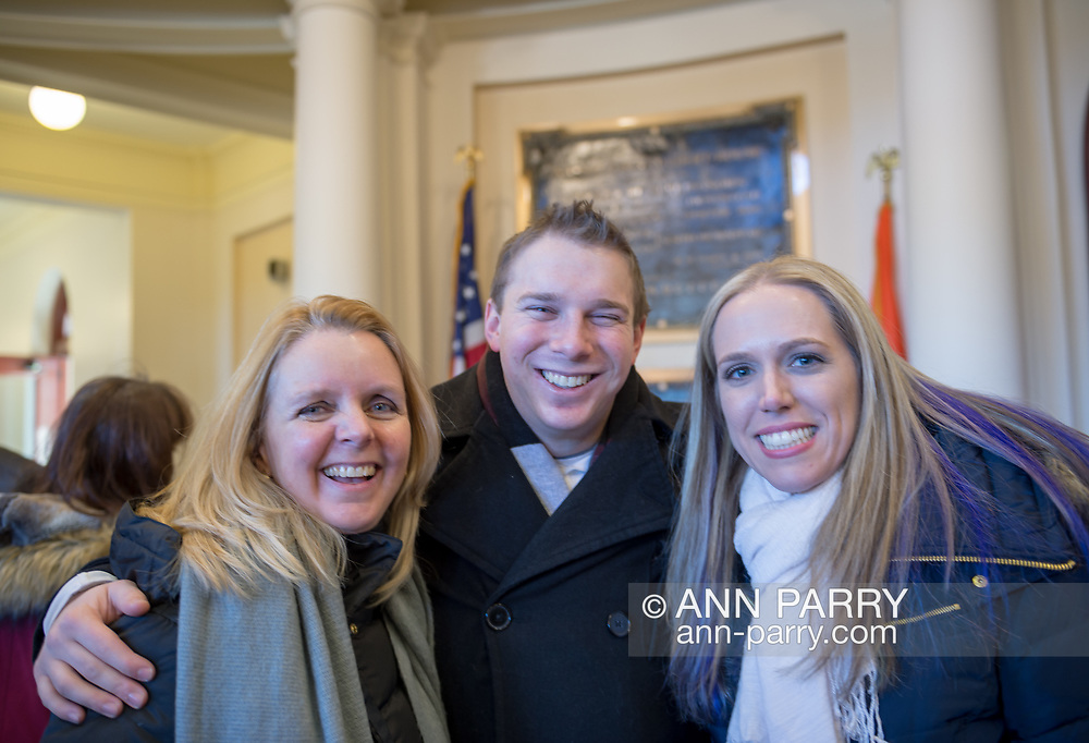 Mineola, New York, USA. January 1, 2018. L-R, Nassau County Legislator DEBRA MULE, 55, (Freeport - 5th District - Democrat), Nassau County Legislator JOSHUA LAFAZAN, 23, (Syosset - 18th District - Independent), and SUE MOLLER, 39, of Merrick, are in Theodore Roosevelt Executive & Legislative Building after attending outdoor swearing-In of Laura Curran as Nassau County Executive. Both first terms legislators, Lafazan is a registered Independent and Nassau County's youngest ever legislator, and Mule has Curran's former Legislative seat. Moller was the Democratic candidate for Hempstead Town Council District 6 in 2017.