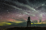 Aurora Australis and stars behind a cloudy night at Waipapa Point Lighthouse, Catlins