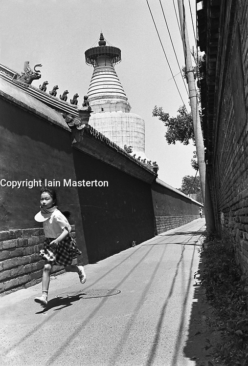 Girl running through hutong in shadow of temple in Beijing China