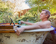 Senior adult man in bathtub looking at iPad in yard.