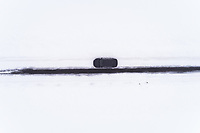 Aerial view of a car driving on a snowy straight road on Vormsi island, Estonia.