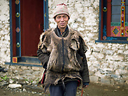 Portrait of a Brokpa man wearing outside the Buddhist temple on an 'auspicious day' in the remote village of Merak in Eastern Bhutan. He is wearing a sleeveless deer skin vest over his 'gho' a traditional long sleeved woollen tunic made from yak wool.